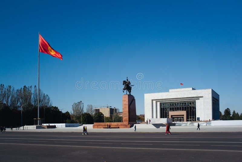 Ala-auch Quadrat, das Kyrgyz Flagge auf Fahnenmast mit Helden Manas Statue und Zustands-Geschichtsmuseums-Standpunkt wellenartig  stockfotografie
