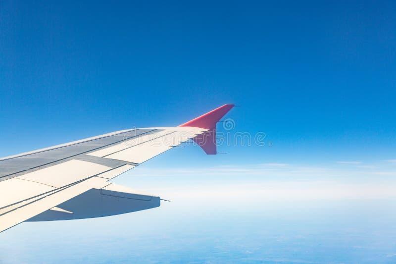 Ala de aviones en las nubes, moscas en el fondo de la ciudad fotos de archivo