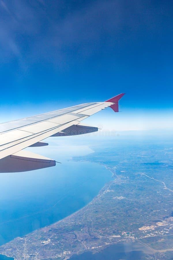 Ala de aviones en las nubes, moscas en el fondo de la ciudad imagenes de archivo