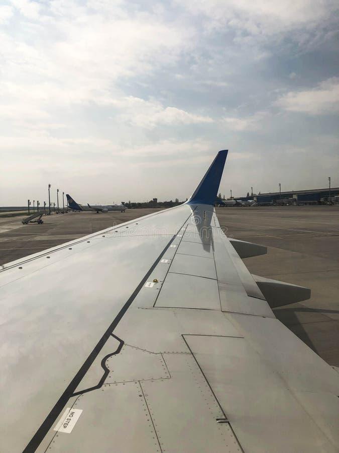 Ala de un aeroplano r?pido hermoso del jet con un motor en la pista en el aeropuerto Foto vertical foto de archivo libre de regalías