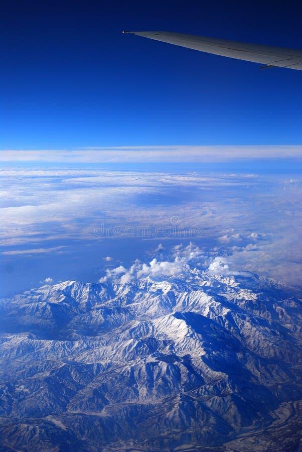 Ala de un avión de pasajeros sobre las montañas fotografía de archivo
