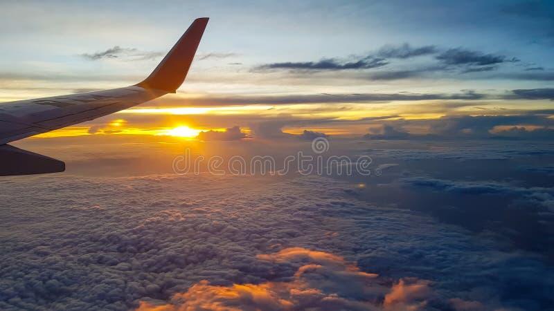 Ala del avión de reacción sobre las nubes en la mucha altitud cuando puesta del sol imagen de archivo libre de regalías