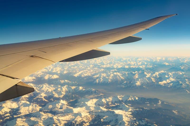 Ala del avión sobre la cubierta de la montaña con la nieve blanca Vuelo del aeroplano en el cielo azul Visi?n esc?nica desde la v fotos de archivo