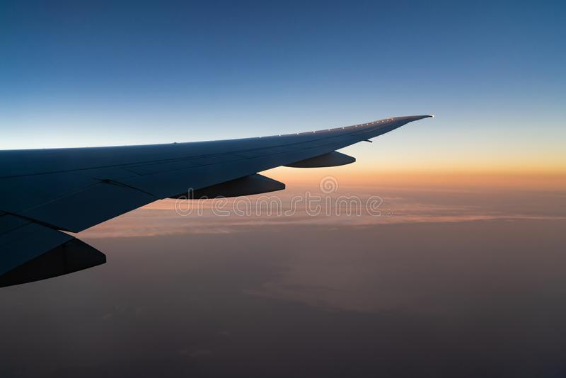 Ala del avi?n sobre la ciudad Vuelo del aeroplano en el cielo azul Visi?n esc?nica desde la ventana del aeroplano Vuelo de la lín imagen de archivo