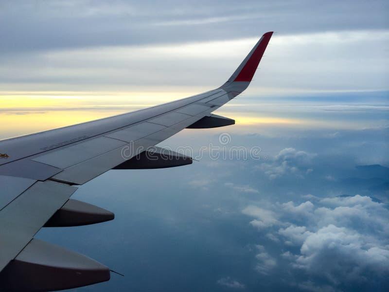 Ala dell'aereo con il cielo nuvoloso su fondo al tramonto immagine stock