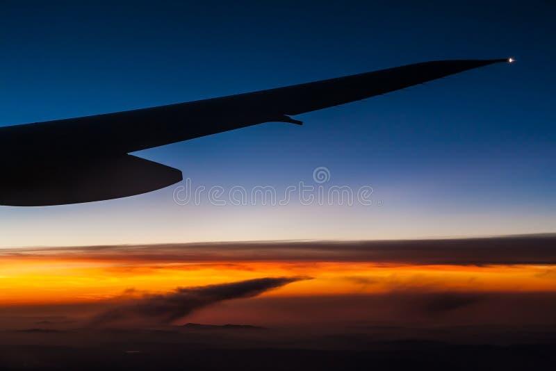 Ala dell'aeroplano sopra le nuvole al tramonto fotografie stock