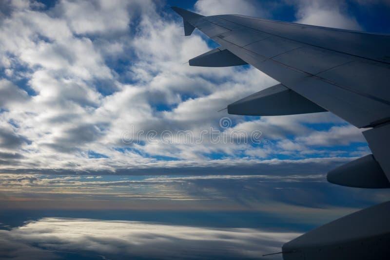 Ala dell'aeroplano in volo, guardando attraverso la finestra immagine stock