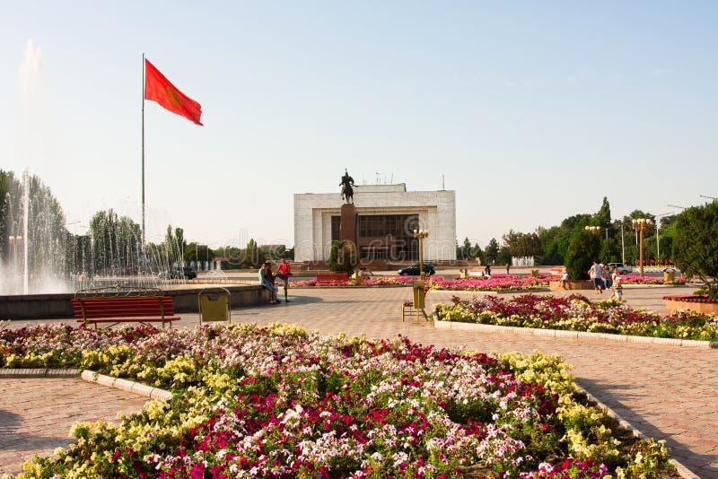 Ala-Demasiado principal del cuadrado de ciudad con los macizos de flores y la bandera nacional de Kirguistán imagen de archivo libre de regalías