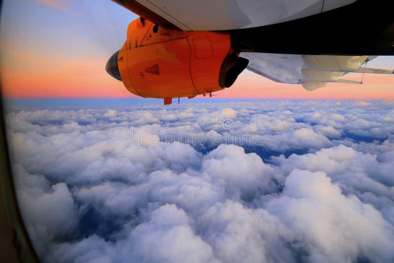 Ala di aereo sopra le nuvole al tramonto fotografie stock