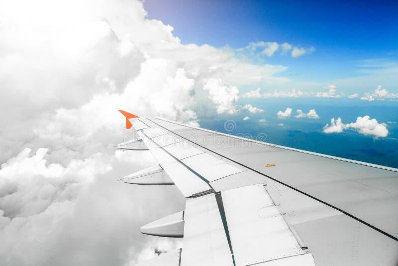 Ala di un volo dell'aeroplano sopra di mattina le nuvole fotografia stock