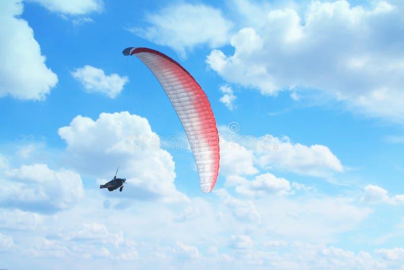 Ala flexible en el mediados de-aire, nubes en el fondo imagen de archivo