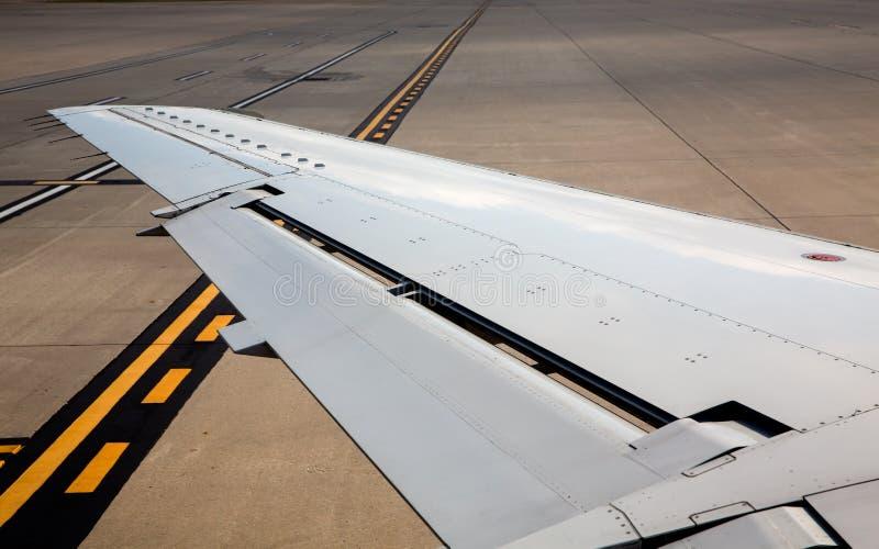 Ala sinistra dell'aeroplano degli aerei sui segni del suolo dell'aeroporto immagine stock libera da diritti