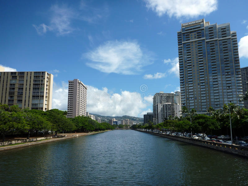 Ala Wai Canal, hotels, Flatgebouwen met koopflats, en bomen op een aardige dag in Waikik stock afbeelding