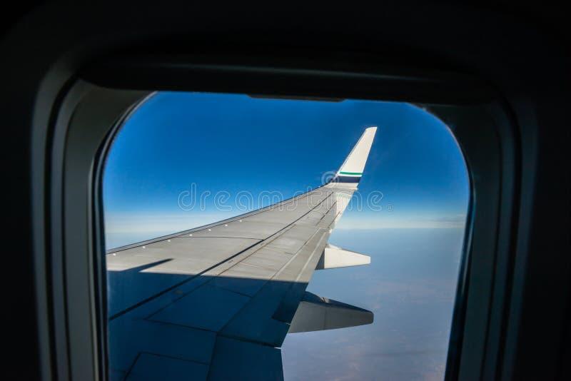 Ala y aletilla del aeroplano en la altitud que cruza, visión desde la ventana fotos de archivo libres de regalías