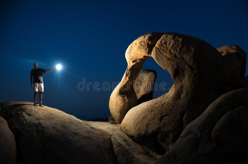 Alabama Hills Arch. Man illuminating the Mobius Arch in Alabama Hills at night royalty free stock photo