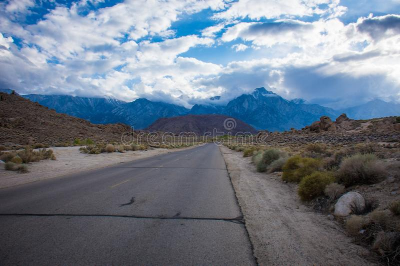 Alabama Hills Recreation Area in Lone Pine California - road through the area with weird rocks and boulders. An approaching storm stock photos