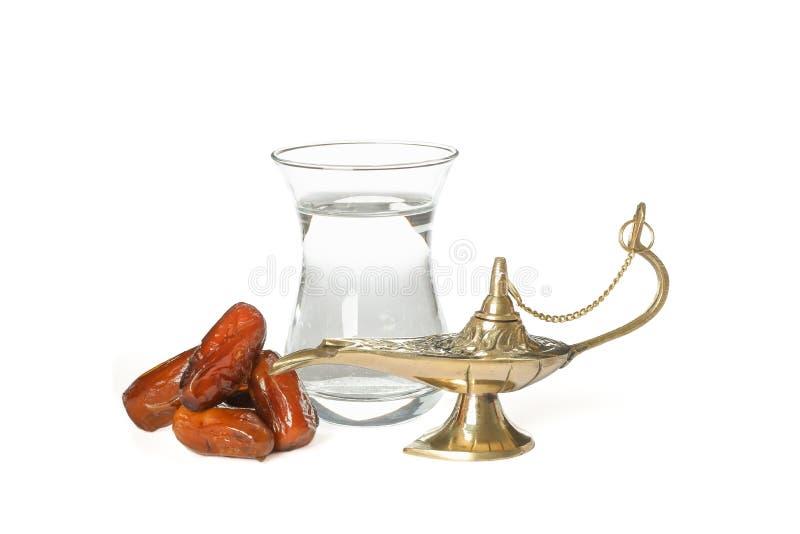 Aladdin Lamp com datas e vidro da água isolado foto de stock royalty free