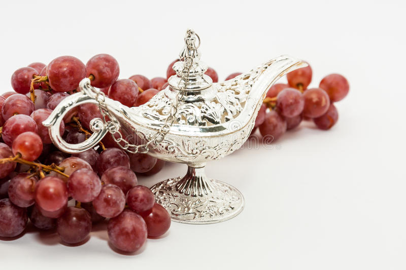 Aladdin's magic lamp and red grapes. Silver Aladdin's magic lamp and red grapes. Ramadan, Eid concept background stock image