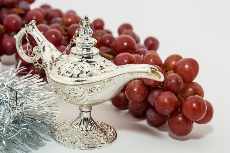 Aladdin's magic lamp and red grapes. Silver Aladdin's magic lamp and red grapes. Ramadan, Eid concept background stock photo