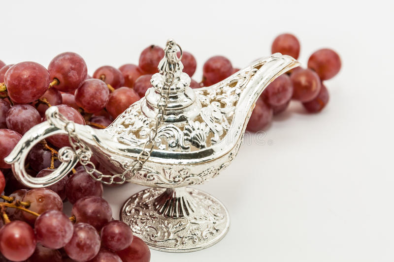 Aladdin's magic lamp and red grapes. Silver Aladdin's magic lamp and red grapes. Ramadan, Eid concept background royalty free stock photos