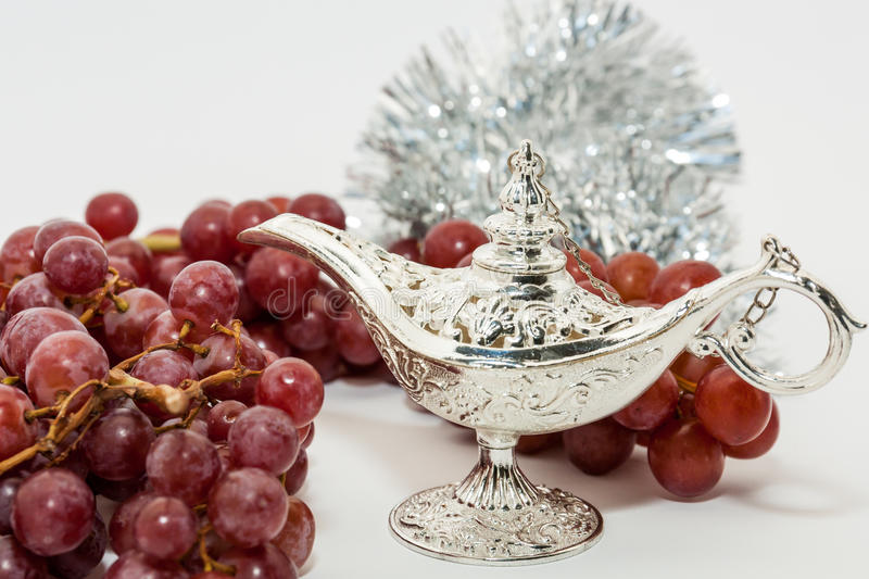 Aladdin's magic lamp and red grapes. Silver Aladdin's magic lamp and red grapes. Ramadan, Eid concept background royalty free stock images