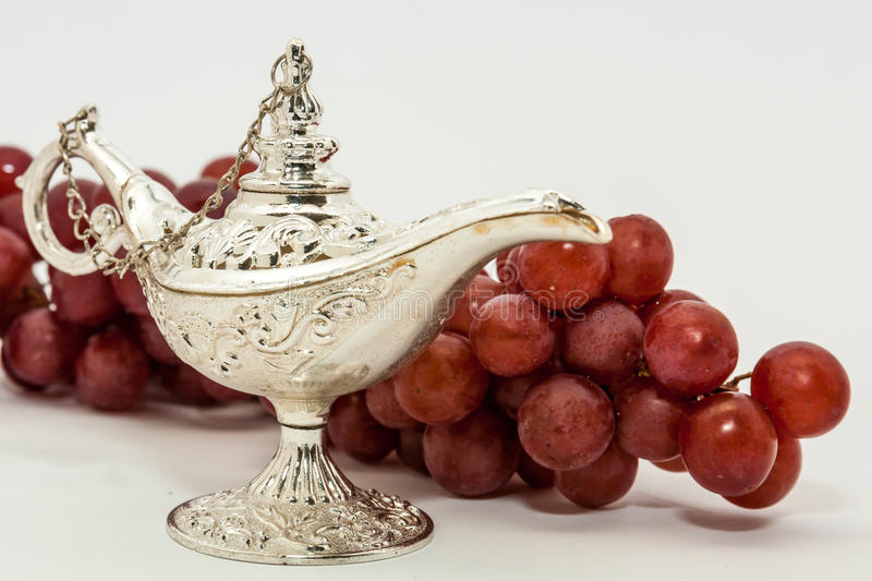 Aladdin's magic lamp and red grapes. Silver Aladdin's magic lamp and red grapes. Ramadan, Eid concept background stock photos