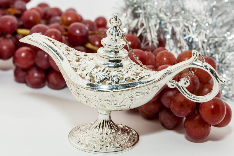 Aladdin's magic lamp and red grapes. Silver Aladdin's magic lamp and red grapes. Ramadan, Eid concept background stock photography