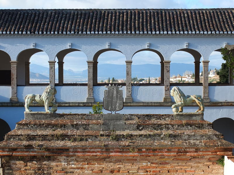 Alahambra's View From Palace To Beyond. The lions stand guard to the palace gardens, with a view through the arches to Granada and the mountains beyond stock photography