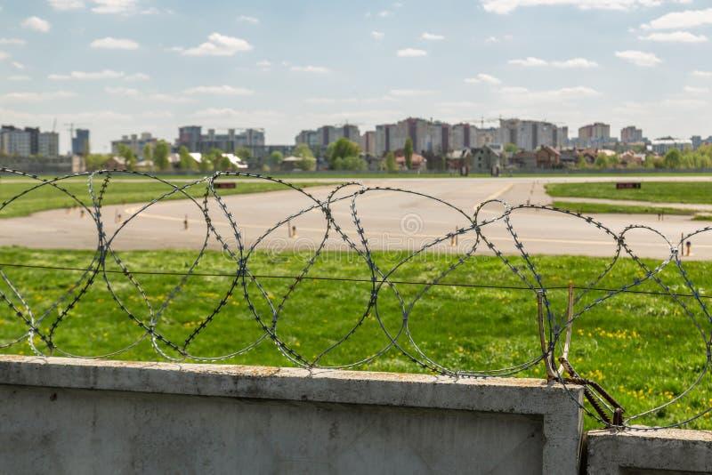Alambre de hormigón con alambre de púas alrededor de la pista de aterrizaje del aeropuerto contra el cielo azul en segundo plano  imagenes de archivo
