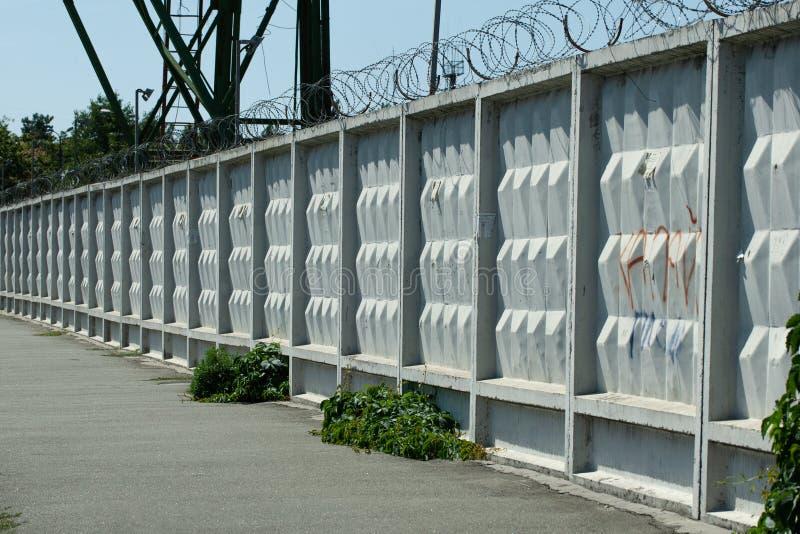 Alambre de hormigón con alambre de púas alrededor de la zona protegida fotos de archivo