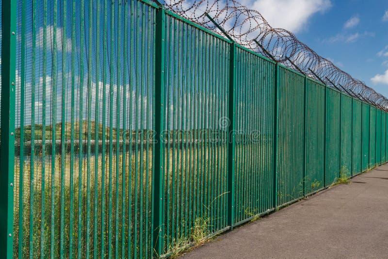Alambre de la maquinilla de afeitar encima de la cerca verde que guarda la terminal de transbordadores francesa imagenes de archivo
