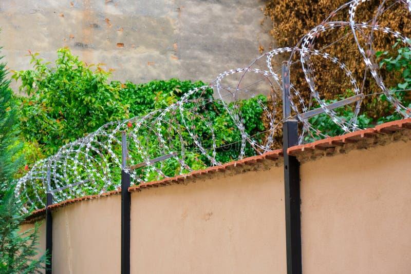 Alambre de púas en una pared, medida de seguridad contra ladrones/intrusos fotografía de archivo