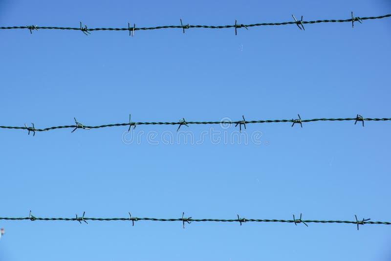 Alambre en espiral de la maquinilla de afeitar con sus lengüetas de acero agudas encima de una cerca de perímetro de la malla ase foto de archivo