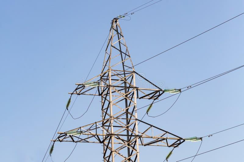 Alambres de la línea eléctrica contra la pieza del cielo azul de la torre del metal imagen de archivo libre de regalías
