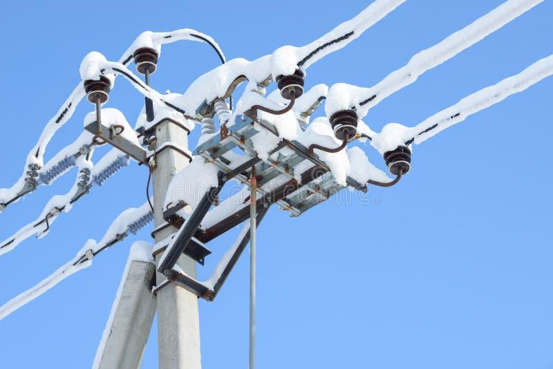 Alambres eléctricos de las comunicaciones cubiertos con hielo y nieve Líneas y polo nevados del cable de transmisión Línea de tra imagenes de archivo