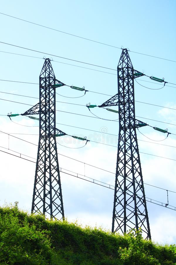 Alambres eléctricos en la cima de torres del metal que alimenta la ciudad foto de archivo
