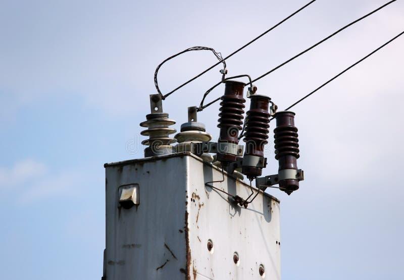Alambres eléctricos que extienden de la estación del transformador cerca del ferrocarril en un fondo del cielo azul fotografía de archivo