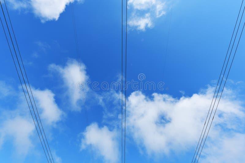 Alambres grandes de la línea eléctrica contra el cielo azul con las nubes imágenes de archivo libres de regalías