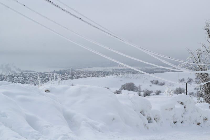 Alambres helados en la helada en la línea eléctrica contra el cielo del invierno de la ciudad imagenes de archivo