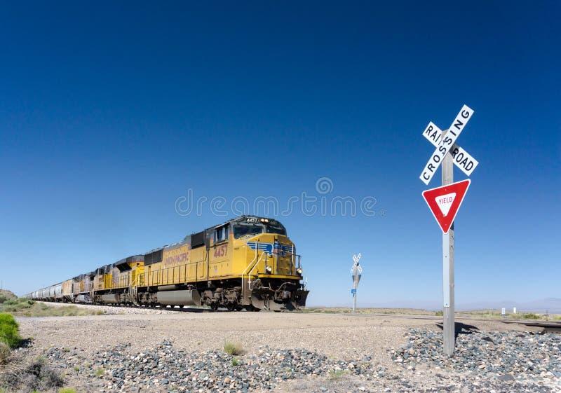 Alamogordo, nanômetro/Estados Unidos - 10 de julho de 2016: O trem de mercadorias pacífico da união cruza um cruzamento de estrad imagens de stock royalty free