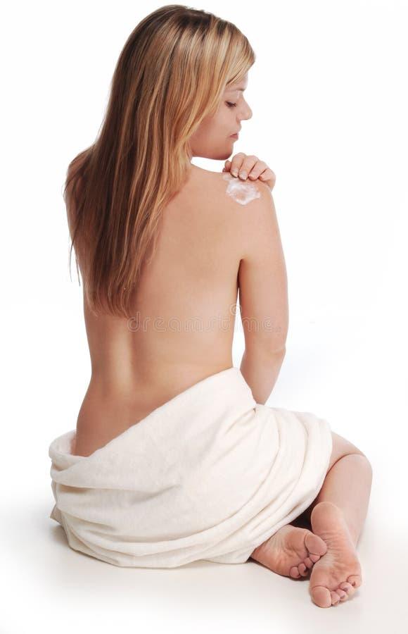 Alana, das Lotion an der Schulter anwendet stockfotos
