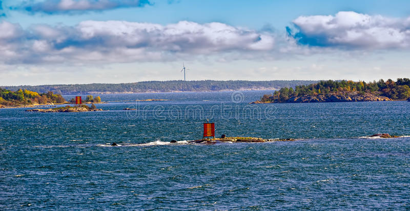 Aland Islands archipelago, Finland. Aland Islands archipelago coastline with navigatiom marks and wind energy power generators at autumn sunny day royalty free stock photos