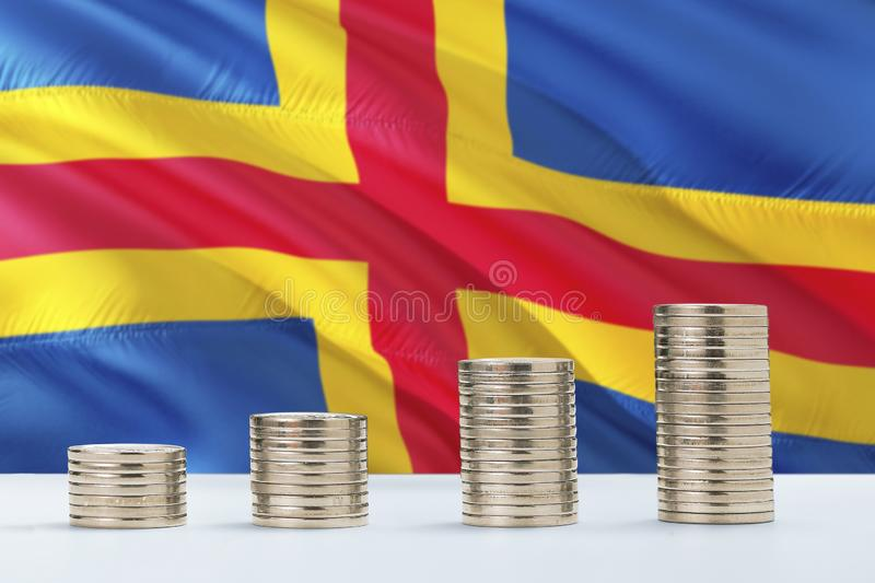 Aland Islands flag waving in the background with rows of coins for finance and business concept. Saving money.  royalty free stock photos