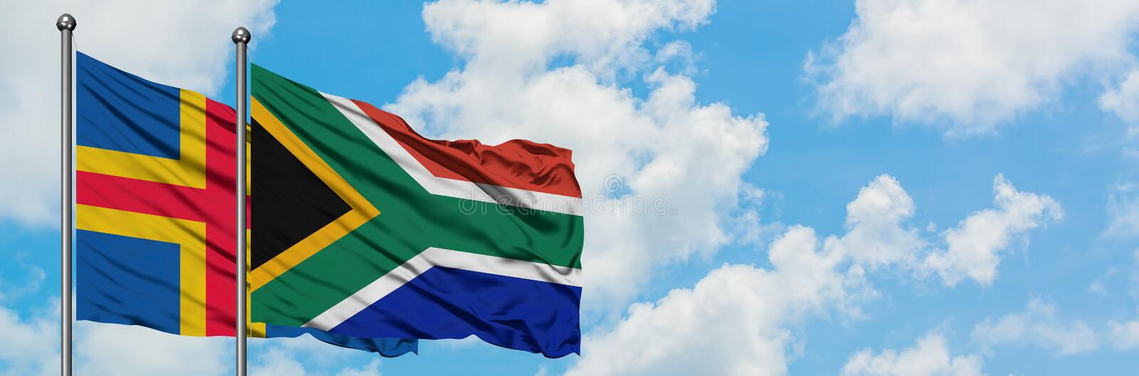 Aland Islands and South Africa flag waving in the wind against white cloudy blue sky together. Diplomacy concept, international royalty free illustration