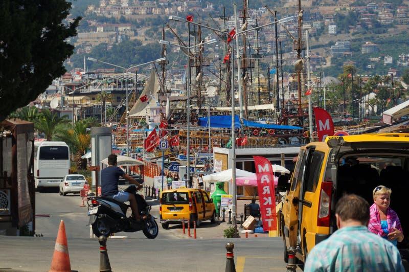 Alanya, die Türkei - 06 26 2015: Reihen von Straßenlaternemasten und Bootsmaste auf der Bank des Mittelmeerhafens herein segeln lizenzfreie stockbilder