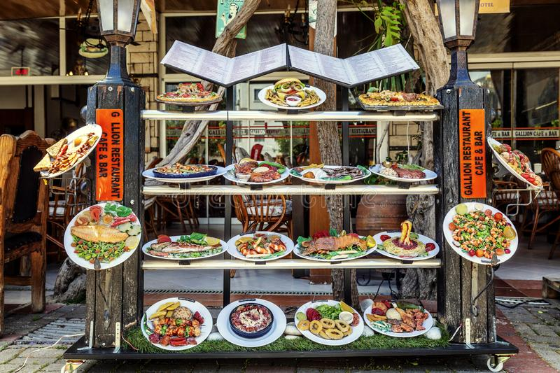 Alanya, Turkey, 05/07/2019: Dummies of dishes from the restaurant menu on the shop window in the street stock image