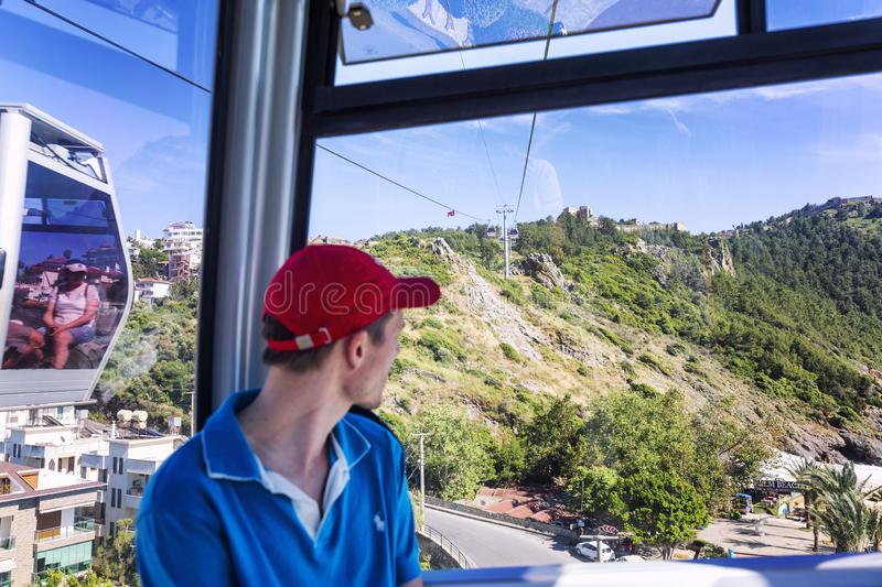 Alanya, Turkey, 05/08/2019: A passenger looks at the beautiful landscape from the cabin of the cable car stock photos