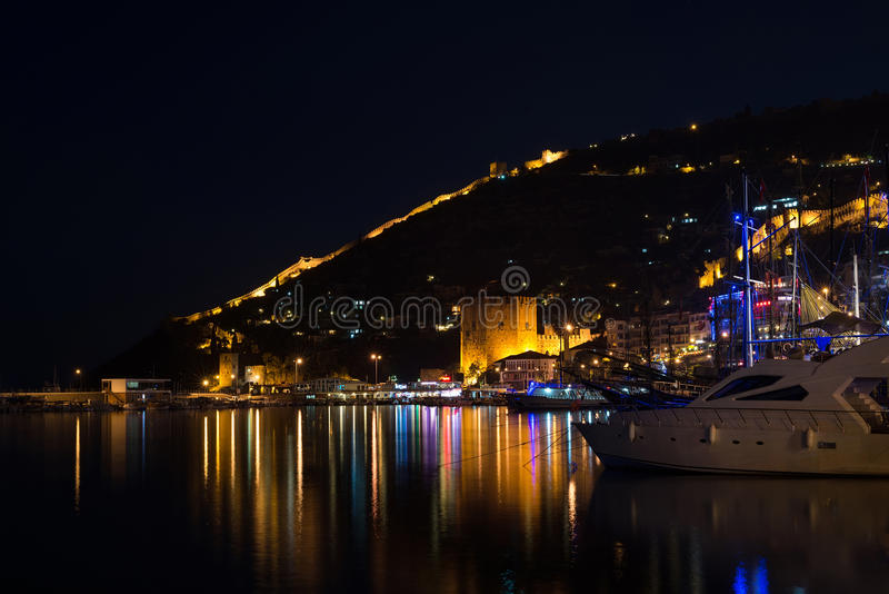 Alanya Turkiet - November 13, 2015: Nattsikt av hamnen, port, det röda tornet och fästningen arkivbilder