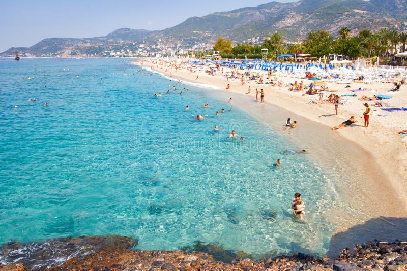 Alanya Turkiet - September 14, 2017: Tropisk havsstrand med simningturister på sommarsemestersemesterort arkivfoton