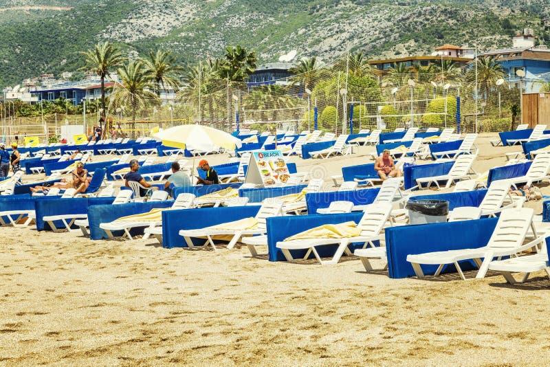 Alanya, Turkije, 05/07/2019: De mensen ontspannen op de lanterfanters op het zandige strand stock afbeelding